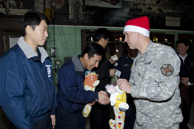 Col. Michael E. Masley, garrison commander for USAG Yongsan, delivers goodies and Christmas cheer to the unsung heroes of Yongsan, Dec. 24. Operation Santa Express is an annual token of appreciation for all the first responders and security forces across Yongsan. (U.S. Army photo by Staff Sgt. Luke Graziani, USAG Yongsan Public Affairs Office)