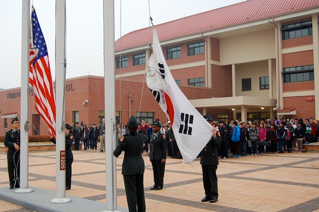 Camp Humphreys Middle/High School JROTC students raise the U.S. and Republic of Korea flags during opening ceremonies for their new campus, Jan 8, 2014.