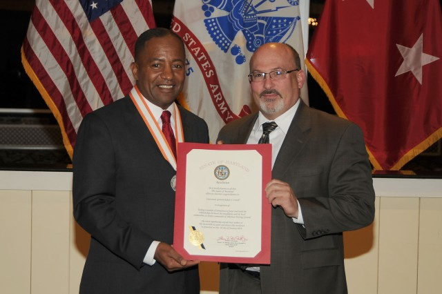 (Right) U.S. Army Communications-Electronics Command (CECOM) Acting Director,  Gary  P. Martin, presents Maj. Gen. (P) Robert S. Ferrell (left), with a signed Senate of Maryland resolution on behalf of President of the Senate Thomas V. Mike Miller, Jr., and state Sens. J.B. Jennings, Barry Glassman, and Nancy Jacobs during a farewell dinner Tuesday, Jan. 7, 2014, at Aberdeen Proving Ground, Md.  Ferrell received Senate confirmation of his third star at the rank of lieutenant general  and new assignment to the position of Chief Information Officer/G-6, Office of the Secretary of the Army Dec. 20.  He relinquished command of CECOM Dec. 23.