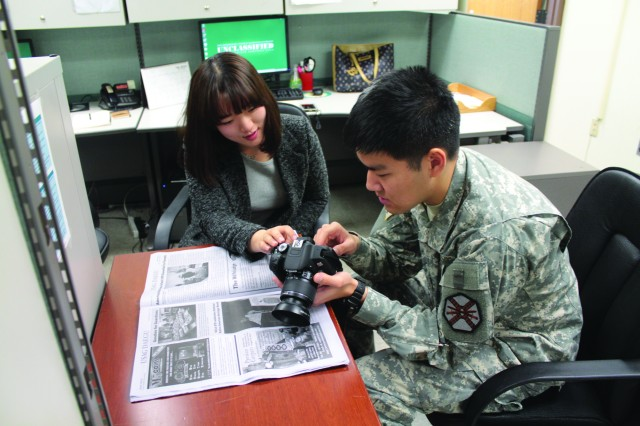 USAG Daegu Public Affairs intern Lee, Jeong yun, a Daegu Haany University student, discusses camera settings with Korean Augmentation to the U.S. Army (KATUSA) Cpl. Chin, Hyun joon, in preparation for covering a story.