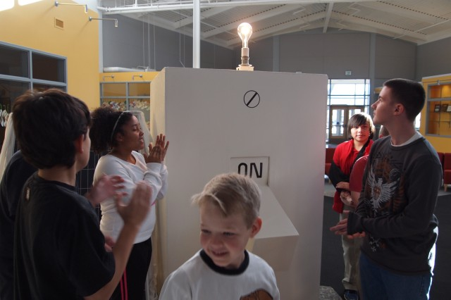 Members of the Cyber Patriots flip a giant switch, turning on a light bulb at Colonel Smith Middle School Dec. 19 during a ceremony to commemorate the completion of solar panel systems at CSMS and Colonel Johnston Elementary School. The switch was hooked up a solar panel to help provide the energy.