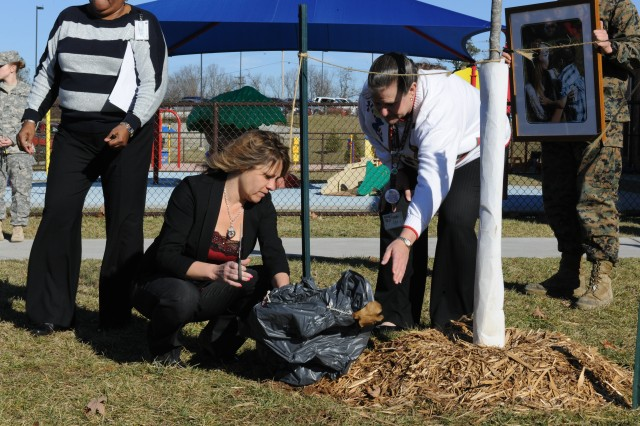 Michelle Lee, Jessica's mother, cuts the wrapping to unveil one of the plaques marking the trees dedicated to the memory of Jessica Lee and her son, Elyjah, who both perished in the flooding last August.