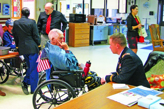 Lt. Col. Daniel Duncan, commander, Army Field Support Battalion-Riley, of Fort Riley, Kan., visits with a veteran Dec. 18 at the Veterans Affairs Medical Center, Topeka, Kan. (Courtesy photo)
