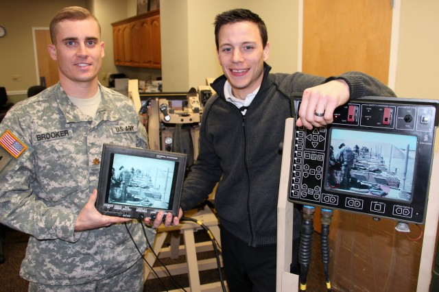 Assistant Product Manager Maj. Curtis Brooker and Common Remotely Operated Weapons Station, or CROWS, Engineer Matthew Moeller demonstrate the second screen option developed at Picatinny Arsenal, N.J.  Army Acquisition professionals from Product Manager Crew Served Weapons helped develop and field a cabling system to route the video signal from the CROWS gunner's fire control unit in the back of a tactical vehicle to the Driver's Vision Enhancer screen situated in the front of a vehicle. This  provides other team members the same situational awareness as the gunner. CROWS provides added sensor capability to the DVE system to include 360 degree traverse and elevated point of view. Units can request the second screen cabling system via an operational needs statement.