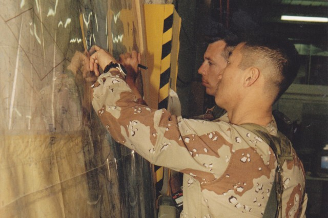 Army Intelligence Soldiers post Iraqi positions on a map during Operation Desert Storm.