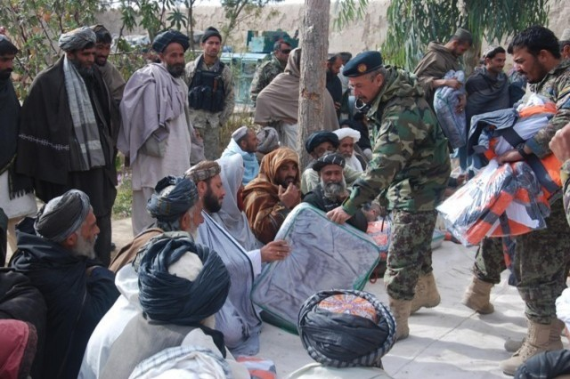 Soldiers from the Afghan National Army distribute coats and blankets to local Afghans during Operation Chamtoo, December 2013. Afghan National Security Forces conducted the operation across four provinces in southern Afghanistan simultaneously, discovering weapons and improvised explosive devices while clearing areas of insurgents.