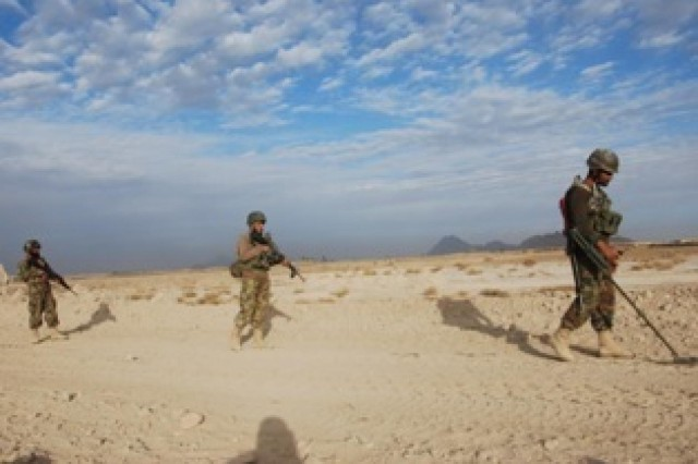 Afghan National Army soldiers provide security while another Soldiers sweeps for mines during Operation Chamtoo, December 2013. Afghan National Security Forces conducted the operation across four provinces in southern Afghanistan simultaneously, discovering weapons and improvised explosive devices while clearing areas of insurgents.