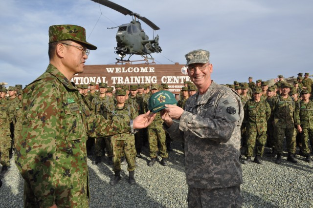 Col. Kazuhiro Yoshihara, deputy commander of Fuji Training Center, Japanese Ground Self Defense Force, presents a baseball cap with his center's logo to Brig. Gen. Ted Martin, National Training Center's commanding general. Yoshihara and about 180 JGSDF Soldiers arrived at Fort Irwin on Jan. 10 to partner with 3rd Stryker Brigade, 2nd Infantry Division during its four-week training rotation at Fort Irwin's National Training Center.