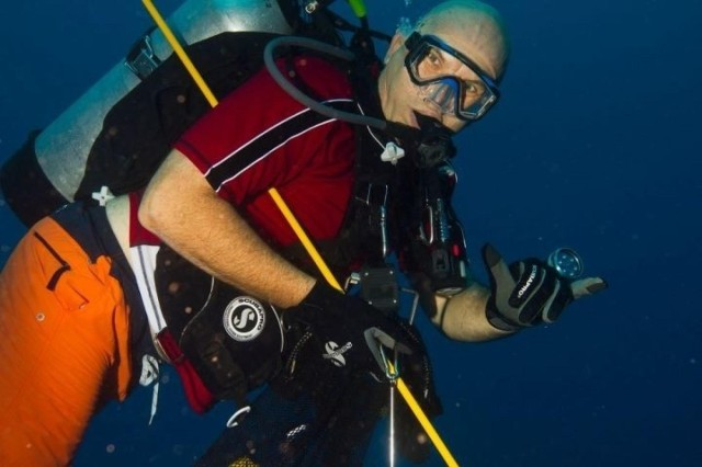 """Col. Dave Neetz, the retiring 8th Theater Sustainment Command's chaplain, gives the """"shaka"""" sign while on a dive along the Hawaii reefs. Neetz recently retired after 40 years of active duty service. (Courtesy photo)"""