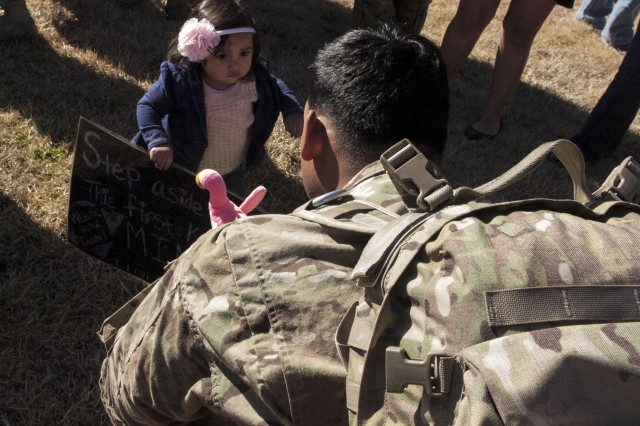 "One-year-old Sophia makes her way to her father, Spc. James Morena, an armorer assigned to Forward Support Company E, 1st Battalion, 5th Cavalry Regiment, 2nd Brigade Combat Team, 1st Cavalry Division, during a welcome home ceremony at Cooper Field at Fort Hood, Texas, Jan. 14. ""I'm speechless,"" said Morena, a native of Houston. ""I can't believe how big she is."" During the ceremony, 81 Soldiers assigned to the 2nd BCT reunited with their Family and friends.  (U.S. Army photo by Sgt. Angel Turner, 1st Cav. Div. PAO (Released)"