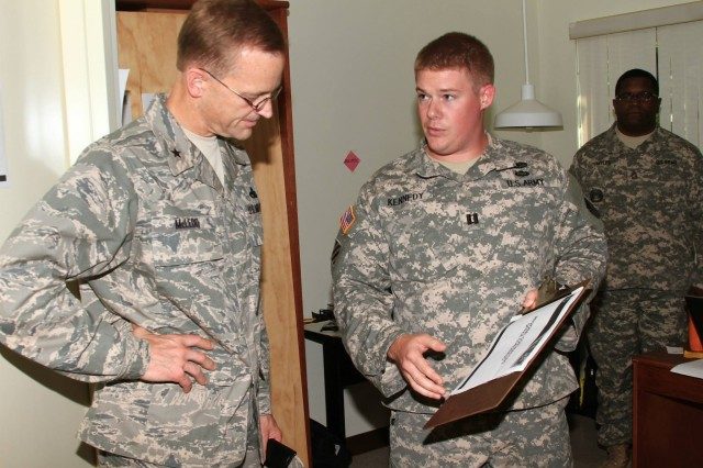 U.S. Air Force Brig. Gen. Mark M. McLeod (left), director, Logistics, Engineering and Security Cooperation, Headquarters, U.S. Pacific Command, receives a briefing on regional contracting center operations from Capt. Jonathan Kennedy, 413th Contracting Support Brigade, during the exercise.