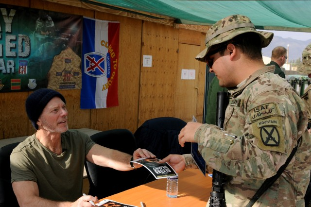 """LAGHMAN PROVINCE, Afghanistan """" Actor Stephen Lang signs an autograph for U.S. Army Pfc. Nathan Tornero on a flyer for his play Beyond Glory, a collection of stories about  Medal of Honor recipients from World War II, Vietnam, and Korea, after performing a few scenes from the show for the service members at Forward Operating Base Gamberi Jan. 13, 2014. Lang travelled to Gamberi accompanied by two of the men whose stories are featured in his production, Medal of Honor recipients Don Jenkins and Walter Marm Jr. Tornero serves as a paralegal with 4th Brigade Combat Team, 10th Mountain Division, Task Force Patriot, and hails from Apple Valley, Calif. (U.S. Army Photo by Sgt. Eric Provost, Task Force Patriot PAO)"""