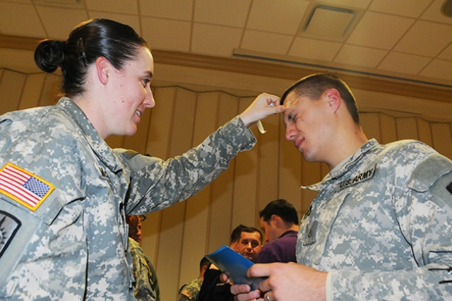 Spc. Britney McCarthy, places a bandage on Pfc. Michael Adams, both of 6th MP Detachment, signifying that their team was physically abused during a practical domestic violence exercise Jan. 10 at Wings Chapel.