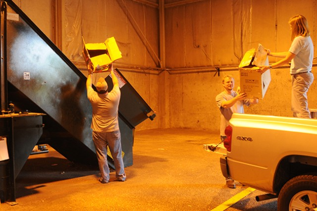 Jason Dykes and Kent Tate, URS contractors, and Melissa Lowlavar, environmental branch chief, begin to unload a truck filled with cardboard and pack it into a baler at the Fort Rucker Environmental Center.