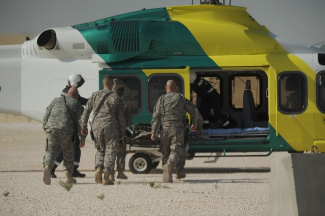 Soldiers transport a patient to host nation paramedics and Life Flight helicopter for evacuation during a medical evacuation exercise in Southwest Asia.