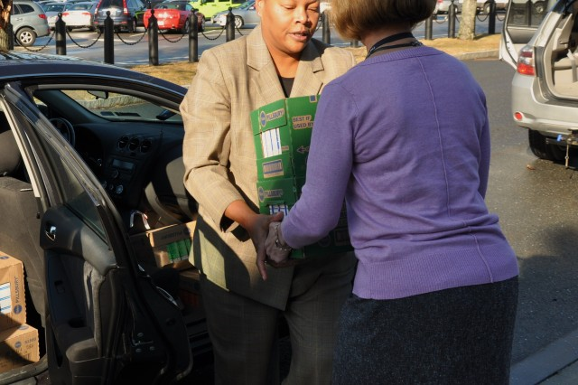Betty Davis and Cindy Dubose shuffle boxes into a vehicle to be delivered to the Worcester County Food Bank Jan. 15. The Natick Soldier Systems Center Equal Employment Office observed the holiday with a day of service in honor of Dr. Martin Luther King Jr.