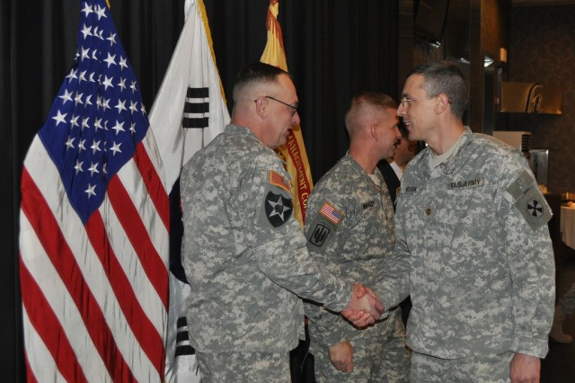Col. Michael. E. Masley, commander of U.S. Army Garrison Yongsan, and Command Sgt. Maj Daniel. L .Willing shake hands with Yongsan community members, thanking their assistance towanrds the garrison during the New Year's reception held at the R&R Bar and Grill. Jan. 16. (U.S. Army photo by Cpl. Jung Jihoon)