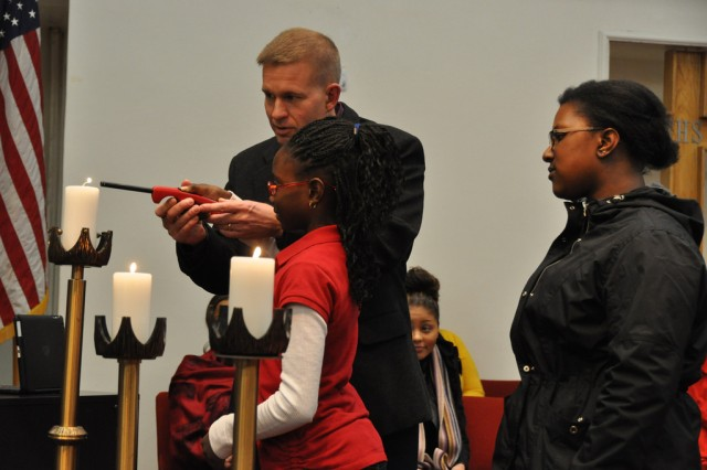 Col. Michael E. Masley, Garrison Commander for United States Army Garrison Yongsan, lights the candles with community children during the Dr. Martin Luther King Jr. Memorial event, Jan 19. (U.S. Army photo by Pfc. Jung Young Ho)