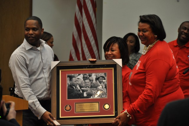 Cynthia M. A. Butler McIntyre, former president of Delta Sigma Theta Sorority (far right) receives a framed commemorative picture of Dr. King during the Martin Luther King Jr. Memorial event, Jan 19. (U.S. Army photo by Pfc. Jung Young Ho)