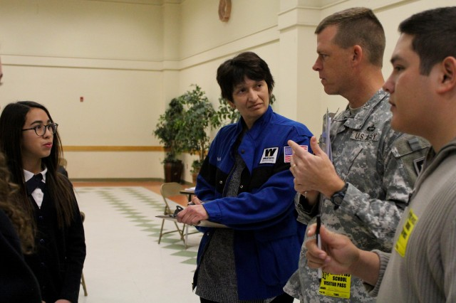 On the right, Tenoch Benitez and Pia Frare from Western Refineries work with Lt. Col. Patrick Hogeboom, commander of 1st Battalion, 361st Engineer Regiment, Task Force Redhawk, 5th Armored Brigade, to grade the science fair project of 8th-graders Veronica Martinez, 13, and Naomi Ramirez, 14, (left). Their project was about the effects of dark colored beverages on teeth and the different whiteners that could be used to counteract stains. St. Pius X School conducts the science fair annually for their 7th- and 8th-graders using help from the local community to judge projects. (Photo by 1st Lt. Vanessa Dudley, 1st Battalion, 361st Regiment, 5th Armored Brigade, Division West Public Affairs)