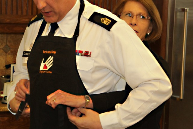 Sgt. Maj. of the Army Raymond Chandler III receives help from his wife, Jeanne, putting on an apron as he prepares to serve breakfast to Wounded Warriors and their families, Jan. 4, 2014, at the Warrior and Family Support Center at Fort Sam Houston, Texas.