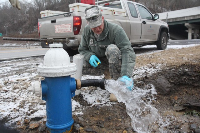 Staff Sgt. Nathan Pettway of the Virginia National Guard's Fort Pickett-based 34th Weapons of Mass Destruction Civil Support Team, collects a water sample, Jan. 19, 2014, in Charleston, W.Va., after Terry Massey, a crew leader with West Virginia American Water, opened the fire hydrant.