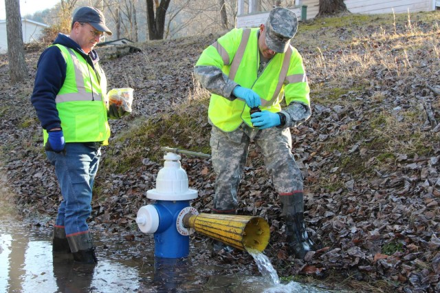 Sgt. 1st Class Scott Wiseman of the Virginia National Guard's Fort Pickett-based 34th Weapons of Mass Destruction Civil Support Team, collects a water sample Jan. 19, 2014, near Charleston, W.Va., after Jeff Miller, a crew leader with West Virginia American Water, opened the fire hydrant. Fourteen Virginia Guard Soldiers and Airmen from the 34th CST are assisting the West Virginia National Guard in the wake of a chemical leak that contaminated the water supply for thousands of residents.