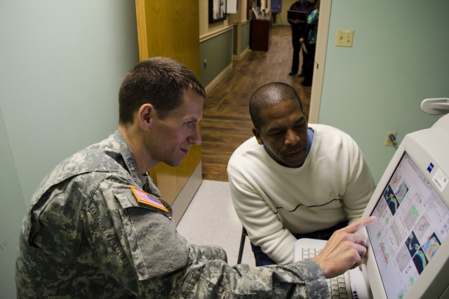 Capt. Bret Lehman, optometrist at Lyster Army Health Clinic, reviews glaucoma reading results with Sgt. First Class Jorge Camarafalu, 597th maintenance detachment, during a routine eye exam Jan. 17.