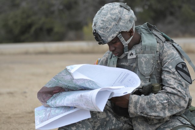 Sgt. Joseph Woods, a Soldier with the 3rd Battalion, 8th Cavalry Regiment, 3rd Brigade Combat Team, 1st Cavalry Division, demonstrates his map-reading knowledge during the Noncommissioned Officer of the Quarter competition, Jan. 10, at Fort Hood, Texas. The Dallas native must determine the curved and straight-line distance of the six-mile route he is marching on. (U.S. Army photo by Spc. Brandon Banzhaf, 3rd BCT PAO, 1st Cav. Div.)