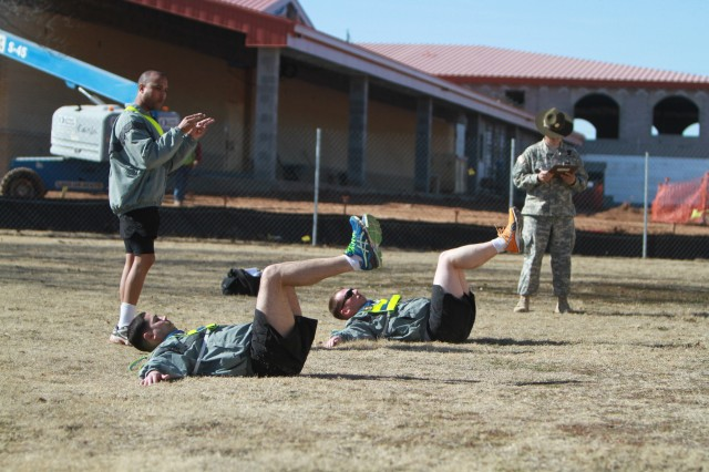 """Staff Sgt. Isaac Dawson, 15th Transportation Company, 100th Brigade Support Battalion, acts as the assisting instructor Jan. 17 during Physical Readiness Exercise. His job was to make sure """"trainees"""" were performing each exercise correctly."""