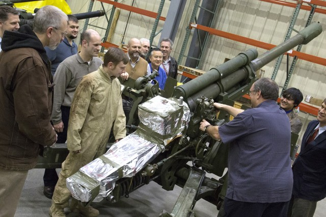 Kenneth Whitnall, Canadian Army Life Cycle material manager for 105 mm Howitzer Fleets, explains to members of the Armament Research, Development and Engineering Center how to conduct maintenance on the C3 Howitzer.