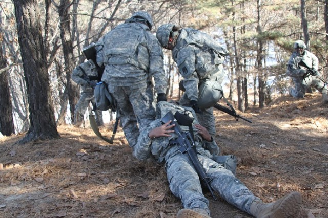 Two medics with Headquarters and Headquarters Battery, 6-52 ADA BN, Pfc. Joel Joseph (left), and Spc. Jennifer Stobb (right), work together to move fellow medic, Spc. Siu Leatoa, who was simulating an injured Soldier during  counter improvised explosive device training at Warrior Base, South Korea, Jan. 13. The Soldiers also fired their various weapons systems at Warrior Base's live-fire ranges, practiced operating in a chemically-contaminated environment and visited the Demilitarized Zone, which was a seven minute drive away. (Photo by Pfc. Shin, Young-Jae, 6-52 ADA Public Affairs)
