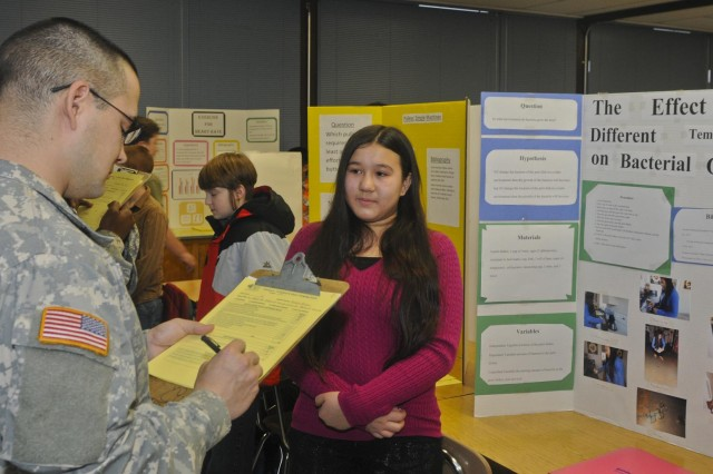 Jessica Niemi, a 6th-grader at Mann Middle School, nervously looks on a science fair judge evaluates her presentation Jan. 15. More than 40 soldiers from the 555th Engineer Brigade volunteered to help their community by serving as judges for the school's science fair. (U.S. Army photo by Spc. Leon Cook)