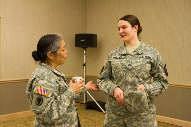 Lt. Col. Celia Florcruz, 7th Infantry Division's Sexual Harassment/Assault Response and Prevention program manager, speaks with a Sgt. Jennifer Phillips, an intel analyst with Headquarters and Headquarters Company, 2nd Stryker Brigade Combat Team, during the Sisters in Arms event at the American Lake Community Center at Joint Base Lewis-McChord, Jan. 7. The event was a forum to educate, train and mentor female soldiers on issues that are unique to them. (U.S. Army photo by Capt. Cynthia R. Holuta, 17th Fires Brigade Public Affairs)