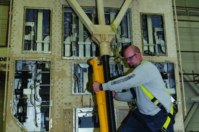 Joe Brungard, an electronics mechanic in Tobyhanna Army Depot's Counter Fire Division, attaches an antenna safety collar to an AN/TPQ-37 Firefinder radar. The device is used to lock the antenna in an upright position while technicians overhaul the Antenna Receiver Group.