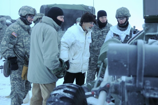 Retired Army Col. Jack Ancker (second from left) and Anchorage area Archdeacon, Father Norman Elliott, both World War II veterans, look over a 105mm Howitzer as paratroopers with the 2nd Battalion, 377th Parachute Field Artillery Regiment, 4th Infantry Brigade Combat Team (Airborne), 25th Infantry Division prepare to fire Dec. 18, 2013 at Joint Base Elmendorf-Richardson, Alaska. Also pictured is the 2-377th's commander Lt. Col. Christopher Ward (left) and the battalion's chaplain, Chaplain (Capt.) Robert W. Davis Jr. (U.S. Army photo by Staff Sgt. Jeffrey Smith/Released)