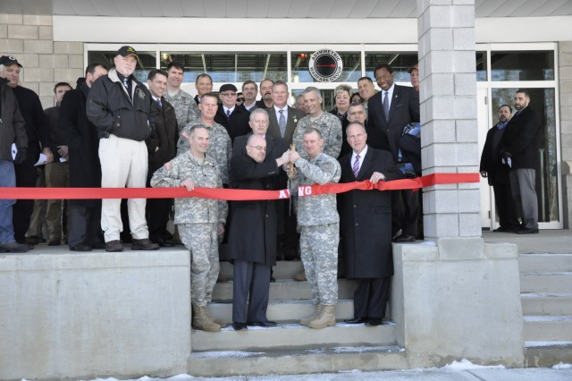 """FORT A.P. Hill, Va."""" The U.S. Army Asymmetric Warfare Group hosts a ribbon cutting ceremony to celebrate the completion of its Asymmetric Warfare Training Center Jan. 24. (Center-Right) Col. John P. Petkosek, commander of the U.S. Army Asymmetric Warfare Group, along with (L-R) Lt. Col. Peter Dargle, Fort A.P. Hill garrison commander,  Adm. (Ret.) John C. Harvey Jr., Virginia Secretary of Veterans Affairs and Homeland Security officially and David Storke, the Bowling Green Mayor, cut the ceremonial ribbon signifying the opening of the state-of-the-art facility. The $96 million dollar facility enhances the AWG's capabilities by providing a location for the unit to replicate complex operational environments and develop solutions to close Army and Joint forces capability gaps."""