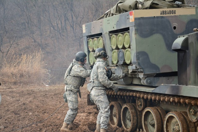 "Staff Sgt. Nathan Mace (right), from Loves Park, Ill., a section chief, and Pvt. Nathan Parham, from Hayward, Calif., a multiple launch rocket system crewmember, both assigned to A Battery, 1st Battalion, 38th Field Artillery Regiment, 210th Fires Brigade, 2nd Infantry Division, secure an ammunition pod into the M270A1 Multiple Launch Rocket System during section certification training Jan. 8, 2014 at Training Area November on Camp Casey, South Korea. The battery conducted a week-long Jan. 6 "" 10 section certification training to qualify multiple launch rocket crewmembers to participate in upcoming live-five exercise. The 210th Fires Brigade is trained and ready to respond to any contingency and to fight tonight and win if called upon."