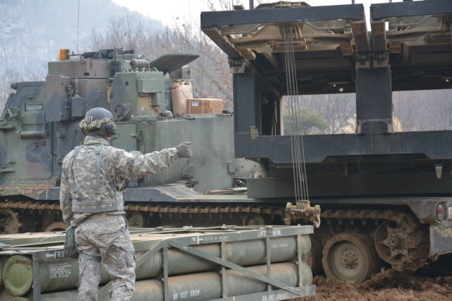 "Staff Sgt. Nathan Mace, from Loves Park, Ill., a section chief assigned to A Battery, 1st Battalion, 38th Field Artillery Regiment, 210th Fires Brigade, 2nd Infantry Division, uses hand signals to unload an ammunition pod into the M270A1 Multiple Launch Rocket System during section certification training Jan. 8, 2014 at Training Area November on Camp Casey, South Korea. The battery conducted a week-long Jan. 6 "" 10 section certification training to qualify multiple launch rocket crewmembers to participate in upcoming live-five exercise. The 210th Fires Brigade is trained and ready to respond to any contingency and to fight tonight and win if called upon."