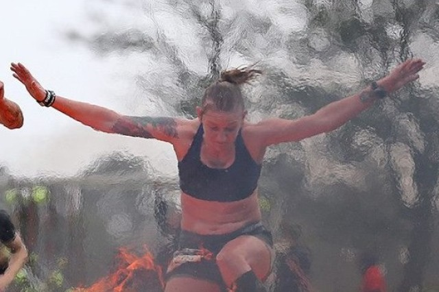 Staff Sgt. Camille Adams leaps over flames and goes on to become the female champion of the 2013 Death Race in Vermont.