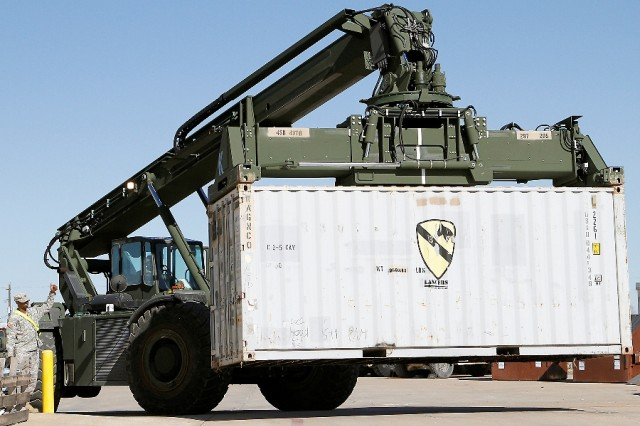 "An RT240 Kalmar Rough Terrain Container Handler moves a shipping container through the 2nd ""Lancer"" Battalion, 5th Cavalry Regiment, 1st ""Ironhorse"" Brigade Combat Team, 1st Cavalry Division, motor pool Jan. 14, at Fort Hood, Texas. Each container moved from Ironhorse motor pools to the Fort Hood Rail Operations Center is another step closer to transporting the brigade to the National Training Center for the upcoming rotation.  (U.S. Army photo by Pfc. Paige Pendleton, 1st BCT PAO, 1st Cav. Div.)"