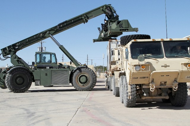 "A Soldier, assigned to the 297th Inland Cargo Transfer Company, 180th Transportation Battalion, 4th Sustainment Brigade, 13th Sustainment Command, uses an RT240 Kalmar Rough Terrain Container Handler to load a shipping container onto a cargo flatbed for the 2nd ""Lancer"" Battalion, 5th Cavalry Regiment, 1st ""Ironhorse"" Brigade Combat Team, 1st Cavalry Division, Jan. 14, at Fort Hood, Texas. Company A,115th ""Muleskinner"" Brigade Support Battalion of the Ironhorse Brigade transported the containers from the Lancer motor pool to Fort Hood's Rail Operations Center in preparation for the upcoming rotation to the National Training Center. (U.S. Army photo by Pfc. Paige Pendleton, 1st BCT PAO, 1st Cav. Div.)"