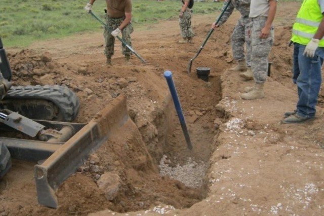 A crew of engineers from the 389th Engineer Company, and the Navy Seabees, work to back-fill a blow-out assembly to a water main line and gate valve to provide running water to a house that never had it before, during Operation Footprint outside of Gallup, N.M., Sept. 3, 2013.