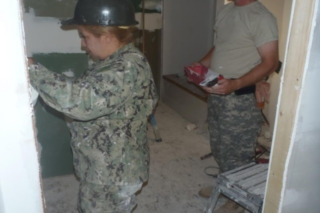 A Navy Seabee and Spc. Michael Cleary, an interior electrician with the 389th Engineer Company, tape and mud the seams of a drywall during a construction project to provide homes for the Navajo Nation in Gallup, N.M., Sept. 5, 2013.