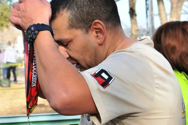 Maj. Michael Noriega, an operations officer at the 2nd Battalion, 393rd Infantry Regiment, dons his medal after completing the half marathon and taking third place for his age bracket during the 11th Annual Miracle Match Marathon in Waco, Texas, Sunday.