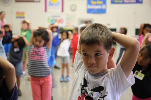 More than 180 Webling Elementary School students join Sgt. Luke Failauga and Pfc. Darrius Scott, both from 8th Special Troops Battalion, for a dynamic physical exercise session at the school in Aiea, Hawaii, Jan. 22.