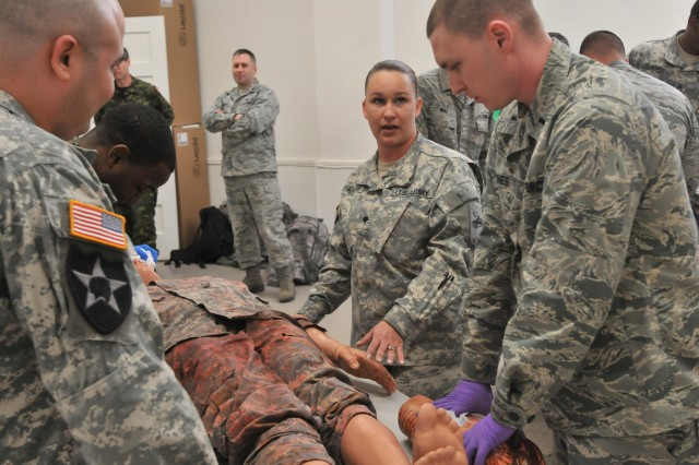 Army Spc. Emma Stevens, a healthcare specialist, speaks to service members taking part in OCSJX-14 as she conducts a first-aid class on how to apply a combat gauze to a casualty with the use of mannequins at the Medical Simulation Training Center. Stevens is assigned to Company C, 123rd Brigade Support Battalion, 4th Heavy Brigade Combat Team, 1st Armored Division at Fort Bliss, Texas.