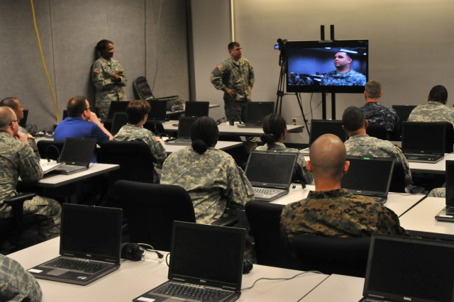 Instructors, civilians and service members observe a video of a mock interview while participating in a public relations class during the Operational Contract Support Joint Exercise 2014 held at Fort Bliss, Texas.