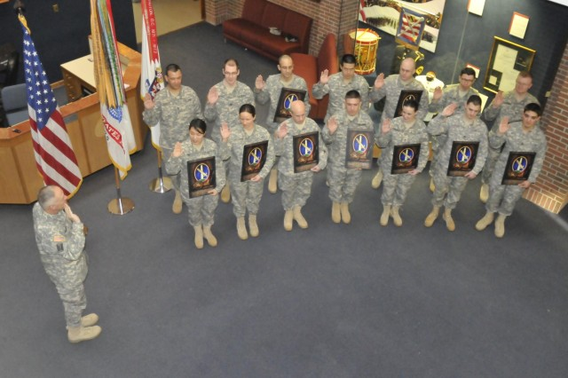 The U.S. Army Band (Pershing's Own) Commander Col. Thomas Palmatier (left) administers the United States Armed Forces Oath of Enlistment to 14 TUSAB staff sergeants during a mass re-enlistment at Joint Base Myer-Henderson Hall's Brucker Hall Jan. 28.