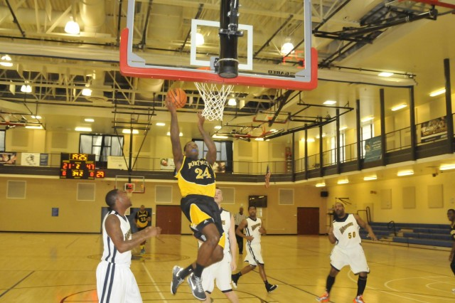 With his blue mouthpiece secure, Fort Myer General Kevin Clark finishes a fast break with a second half layup during the team's 91-60 victory against the NSA Bethesda Warriors Jan. 25 at the Walter Reed National Medical Center fitness center. The game was the Washington Area Military Athletic Conference opener for both teams.
